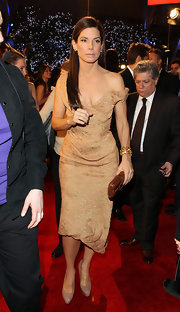 Sandra Bullock paired her nude off-the-shoulder dress with a brown snakeskin box clutch.