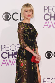 Chelsea Kane accessorized with a red box clutch for a bright spot to her black gown at the 2017 People's Choice Awards.