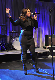 Melanie Amaro performed in a knit black dress and knee-high boots for the pre-Super Bowl party.