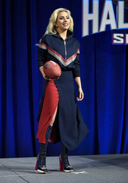 Lady Gaga was sporty and stylish in a tricolor half-zip sweater by Versace at the Super Bowl Ll press conference.