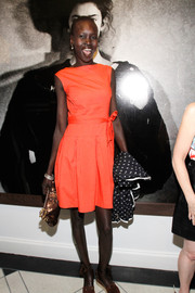 Alek Wek brought a shock of color to the Peter Lindbergh exhibition with this bow-adorned coral dress.
