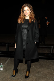 Anna Kendrick added an edgy touch to her classy coat and dress combo with a pair of gold and black ankle boots.
