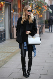 Poppy Delevingne topped off her ensemble with the new Coccinelle B14 tote in black, white, and gray.