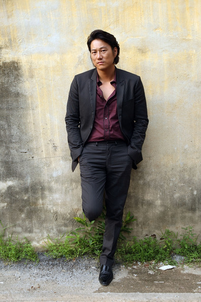 Sung Kang paired a black pinstripe suit with a maroon button-down shirt for a trendy look.