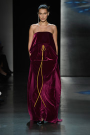 Bella Hadid looked super sophisticated in a strapless burgundy gown with a layered bodice and a gathered waist while walking the Prabal Gurung show.