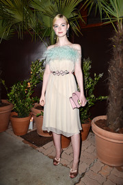 Elle Fanning added an extra pop of pastel with a pink leather clutch.