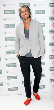 George Lamb can't help but look stylish.  He adds some spunk to his outfit with these bright red canvas shoes.