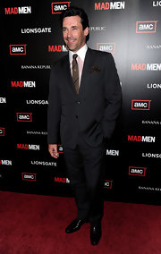 Jon Hamm paired her pink dress shirt with a classic black suit.