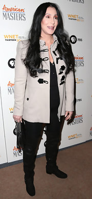 Cher finished off her menswear-inspired ensemble with a pair of black knee-high boots.