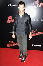 The hunky young actor looked hot in a leather jacket with jeans and lace up, high top sneakers.