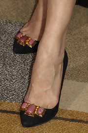 Milla Jovovich posed for photos in black pumps embellished with pink jewels.