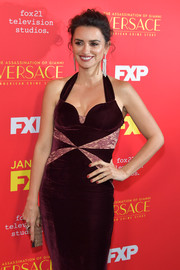 Penelope Cruz paired a glittery gold clutch with a burgundy velvet dress for the premiere of 'The Assassination of Gianni Versace: American Crime Story.'