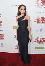 Angelina Jolie stepped away from her head-to-toe blousy black attire and brought out her inner seductress at the Hollywood premiere of 'In the Land of Blood and Honey.' For her directorial debut, she knew the best way to get people talking was to step out in a bombshell gown like this Romona Keveza asymmetrical number.
