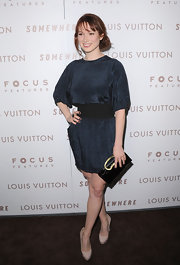 "Ellie Kemper attended the premiere of ""Somewhere"" holding a black patent clutch with a unique gold handle."