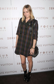Chloe Sevigny looked fashion forward as ever in a pair of black patent cutout booties. She paired the boots with a plaid trench dress.