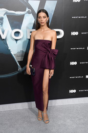 Angela Sarafyan went for sexy glamour in a plum-colored Sophie Theallet strapless dress, featuring a thigh-high slit and a huge bow accent, during the premiere of 'Westworld.'