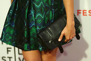 Rashida paired her printed skirt with a cool leather clutch that was adorned with buckle straps.