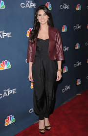 Camila dons a black harem jumpsuit under a cropped leather jacket.