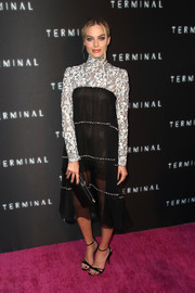 For her bag, Margot Robbie chose a simple black leather clutch.