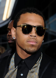 Chris Brown walked the red carpet wearing gold rimmed round sunglasses.