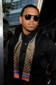 Adding flair to his all black look, Chris Brown paired his black dress shirt with a printed neck tie.