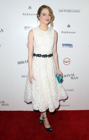Emma Stone injected a pop of color via a turquoise box clutch by Ferragamo.