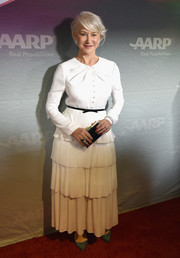 Helen Mirren tied her look together with a black and gold box clutch.