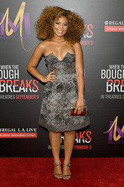 Jaz Sinclair matched her shoes with a metallic gold clutch, also by Jimmy Choo.