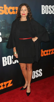 Minnie Driver attended the LA premiere of 'Boss' in a cape-style black coat over a sleek LBD.