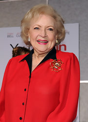 Better White jazzed up her red blouse with a gold brooch.