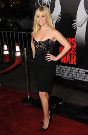 Reese accessorized her embellished cocktail dress with black patent leather stilettos.