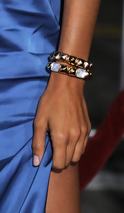 Rosario Dawson paired her sky blue dress with two gold pyramid bracelets while attending the premiere of 'Unstoppable'.