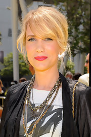 Kristen Wiig paired her graphic t-shirt and leather jacket with gold layered necklaces.