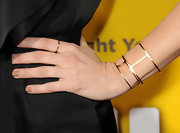 Kristen Wiig added a modern touch to her black silk dress with a gold cuff bracelet.