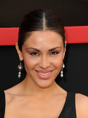 Carla Ortiz paired her sleek center part bun with silver and gemstone earrigns.