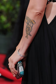 Alanis has a beautiful yellow tiger tattooed to her left forearm.