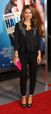 Maria Menounos injected a dose of color into her all black look with a hot pink satin clutch.