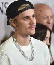 Below his right ear, Justin Bieber sports a vertical tattoo that says 'Patience.'