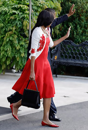 Michelle Obama topped off her elegant retro ensemble with a black leather tote as she left the White House for Fort Stewart.