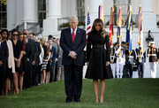 Melania Trump kept it conservative yet elegant in a belted black jacquard coat dress by Michael Kors while participating in a moment of silence for 9/11 victims.