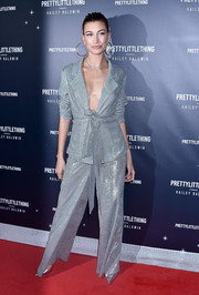 Hailey Baldwin looked totally party-ready in a glittering silver pantsuit at the launch of her PrettyLittleThing collection.