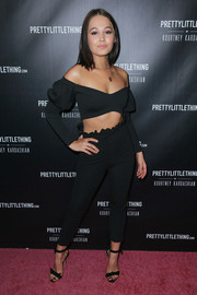 Kelli Berglund completed her all-black ensemble with a pair of knot-detail sandals.