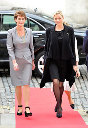 Charlene dons a draped black coat over her LBD for her visit to Ireland.