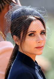 Victoria Beckham paired a veiled navy fascinator with a matching dress for the wedding of Prince Harry and Meghan Markle.
