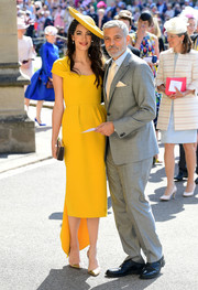 Amal Clooney was vintage-chic in a cap-sleeve mustard frock by Stella McCartney at the wedding of Prince Harry and Meghan Markle.