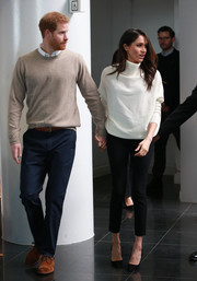 Meghan Markle was casual-chic in a loose white turtleneck by AllSaints teamed with black skinnies while visiting Birmingham.
