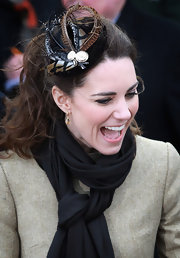 Kate styled up her ensemble with a feathered hair piece for an outing with fiance, Prince William.