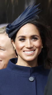Meghan Markle matched her navy coat with a sculptural fascinator by Noel Stewart for Princess Eugenie's wedding.
