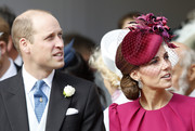 Kate Middleton accessorized with a veiled fuchsia fascinator by Philip Treacy for Princess Eugenie's wedding.