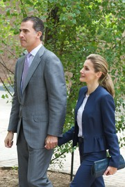 Princess Letizia paired a blue frame clutch with a peplum pantsuit for an official event in Madrid.